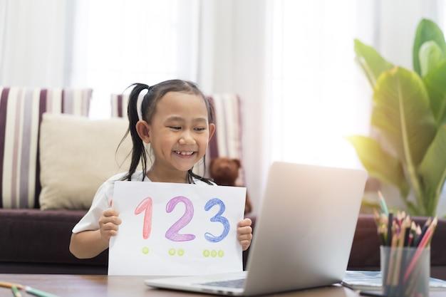 Une petite fille asiatique montre l'apprentissage des devoirs à l'aide d'un ordinateur portable sur internet virtuel en ligne à la maison