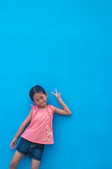 Petite fille asiatique sur le mur bleu