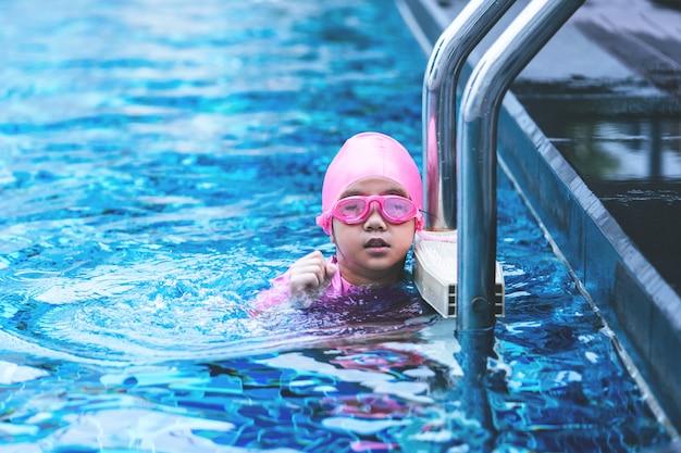 Petite fille asiatique nage avec des lunettes sur l'échelle