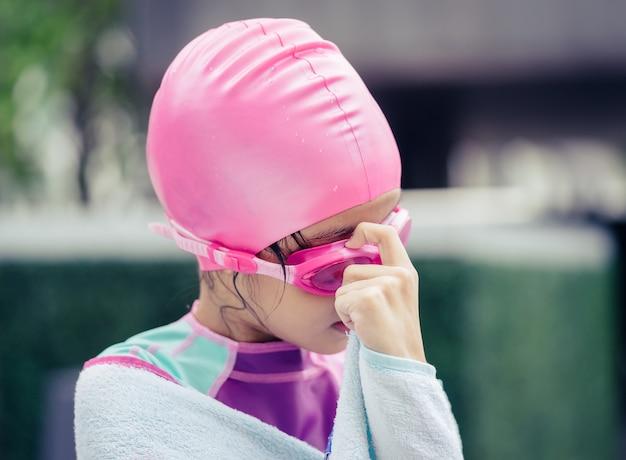Petite fille asiatique nage avec des lunettes