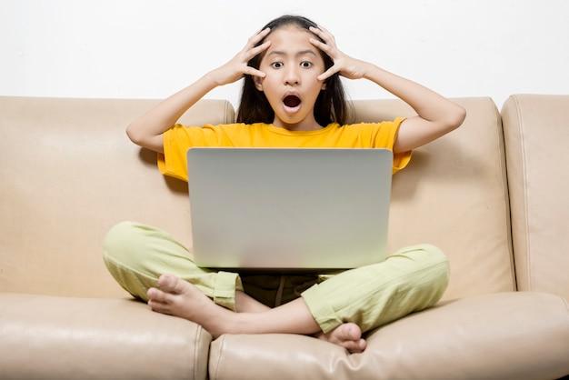 Petite fille asiatique avec un ordinateur portable choquée lors d'un cours en ligne à la maison. éducation en ligne pendant la quarantaine