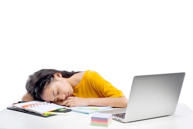 Petite fille asiatique avec ordinateur portable s'endort sur une classe d'école en ligne isolée sur fond blanc. éducation en ligne pendant la quarantaine
