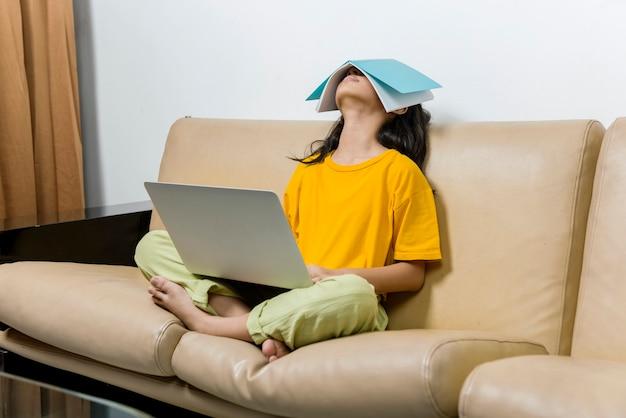 Une petite fille asiatique avec un ordinateur portable s'endort dans un cours en ligne à la maison. éducation en ligne pendant la quarantaine