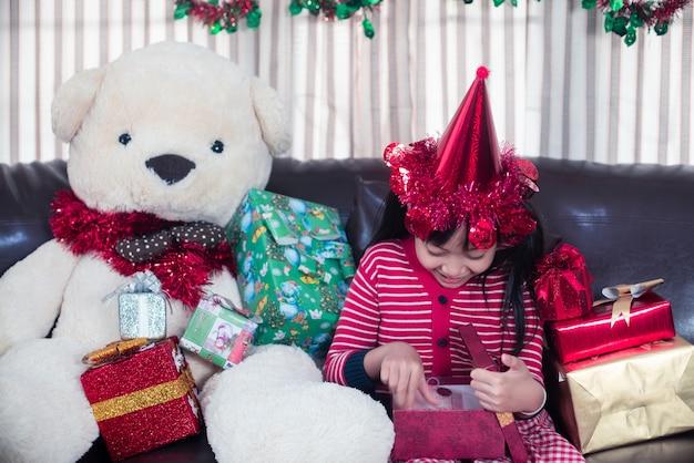 Petite fille asiatique ouvre une boîte-cadeau avec le sourire et heureux le jour de noël
