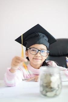Petite fille asiatique portant un chapeau diplômé mettant la pièce dans un bocal en verre transparent tirelire