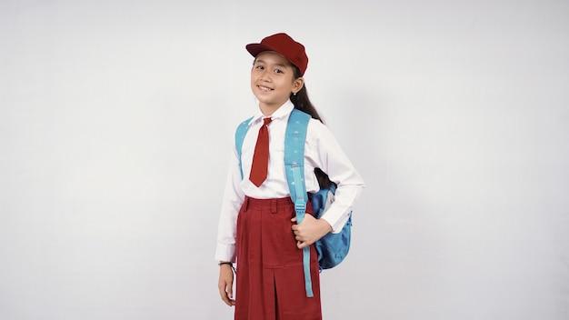 Petite fille asiatique portant un chapeau et un sac d'école souriant joyeusement sur fond blanc isolé