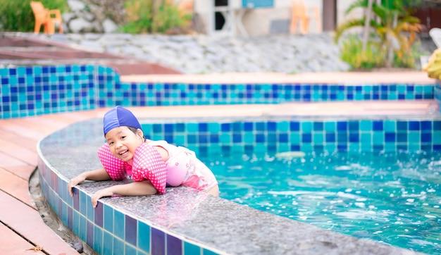 Petite fille asiatique portant des manches gonflables jouant dans la piscine