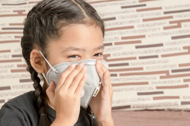 Petite fille asiatique portant un masque n95