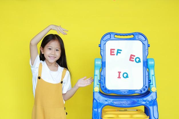 Petite fille asiatique présente quelque chose sur tableau blanc
