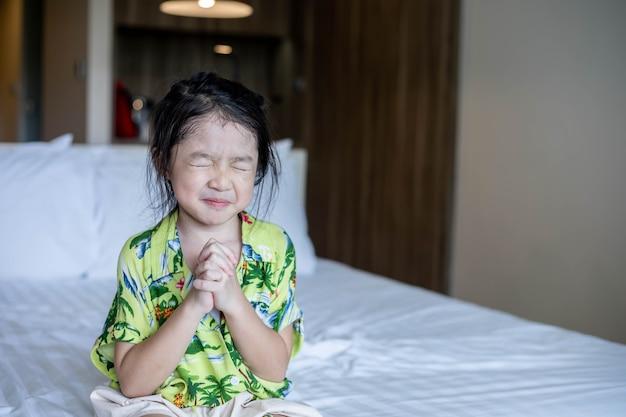 Petite fille asiatique priant à la main, mains jointes dans le concept de prière pour la foi, la spiritualité et la religion.