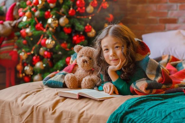 Petite fille asiatique en pyjama dans la chambre allongée sur le lit près de l'arbre de noël en lisant un livre