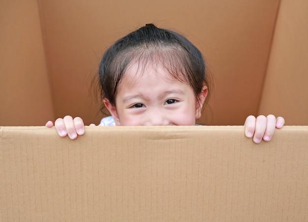 Petite fille asiatique qui joue coucou et se trouve dans une grande boîte en carton.