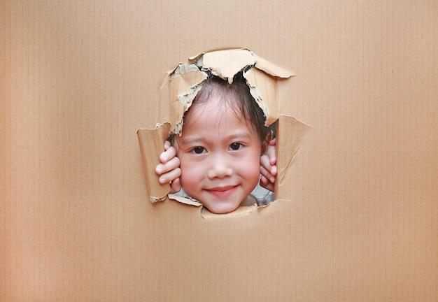 Petite fille asiatique, regardant à travers le trou sur le carton.