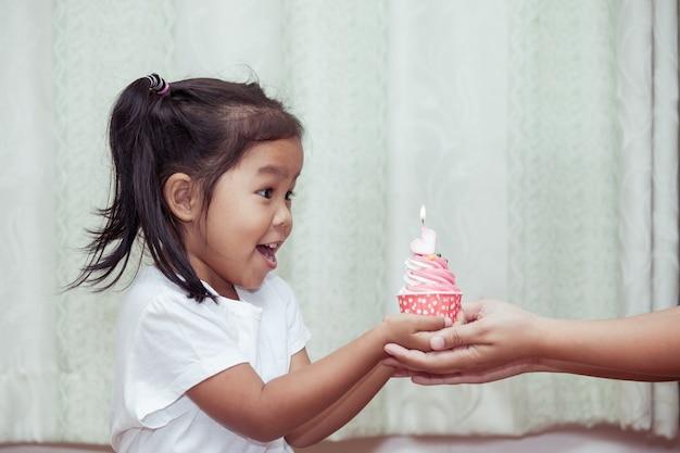 Petite fille asiatique s'amuser à souffler le gâteau d'anniversaire dans le ton de couleur vintage