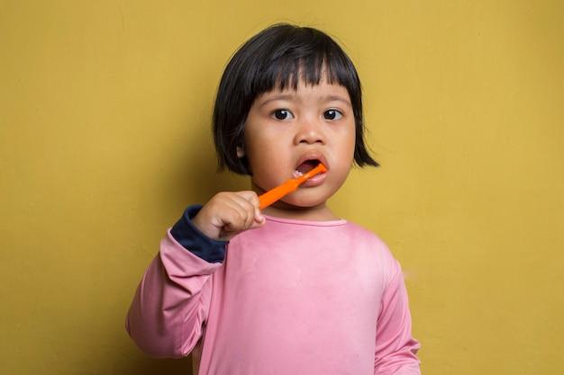 Petite fille asiatique se brosser les dents sur le mur jaune