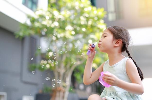 Petite fille asiatique soufflant des bulles de savon dans le jardin en plein air.