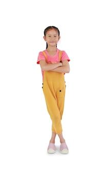 Une petite fille asiatique souriante a croisé les bras et les jambes debout et regardant la caméra isolée sur fond blanc. pleine longueur avec chemin de détourage