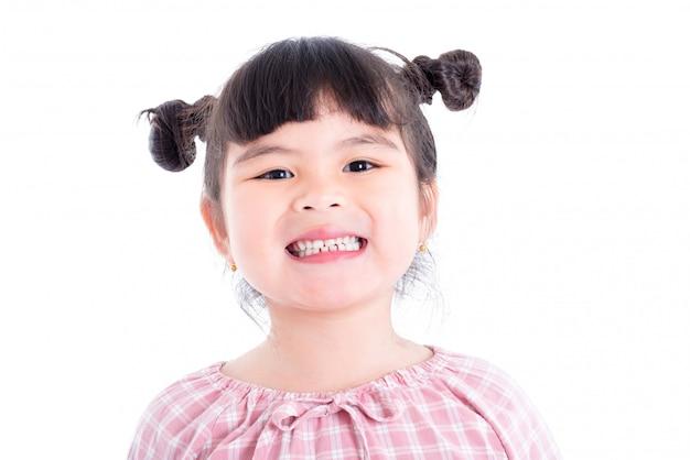 Petite fille asiatique souriante et montrant ses dents sur fond blanc