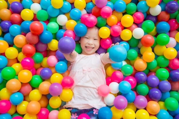 Petite fille asiatique souriante en position couchée sur de nombreuses billes de couleur à l'intérieur de l'aire de jeux