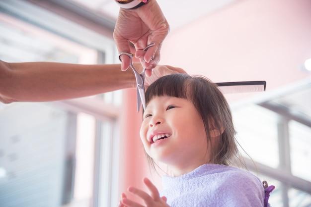 Petite fille asiatique souriante tandis que le coiffeur coupe ses cheveux