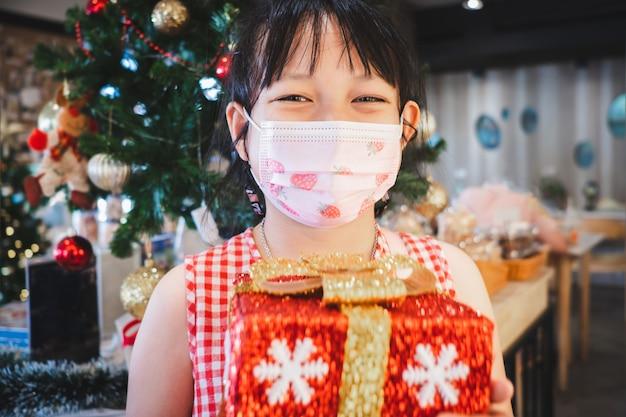 Petite fille asiatique tenant une boîte-cadeau avec un masque facial le jour de noël