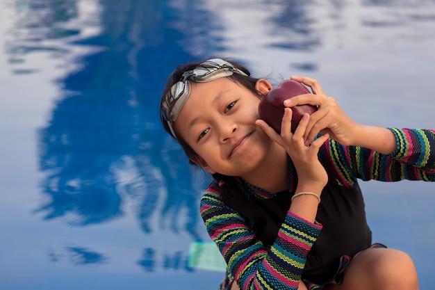 Petite fille asiatique tenant la pomme à la piscine avec des lunettes de natation
