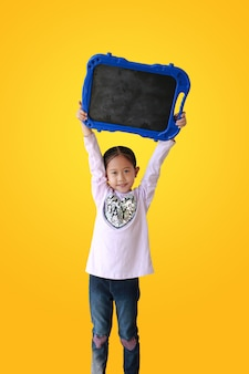 Petite fille asiatique tenant un tableau noir blanc