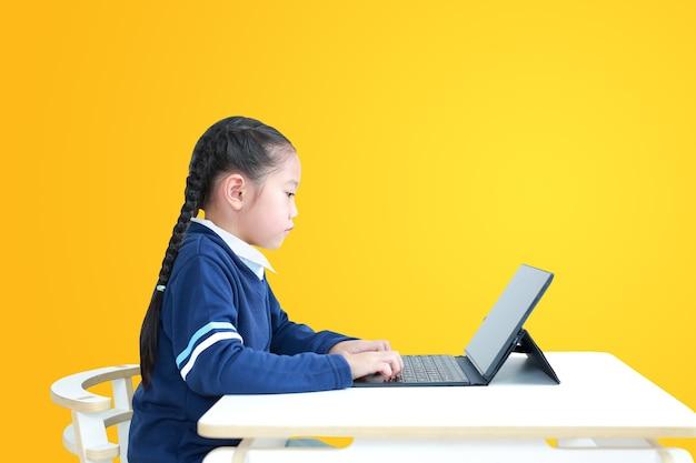 Petite fille asiatique en uniforme scolaire à l'aide d'un ordinateur portable sur la table isolée sur jaune