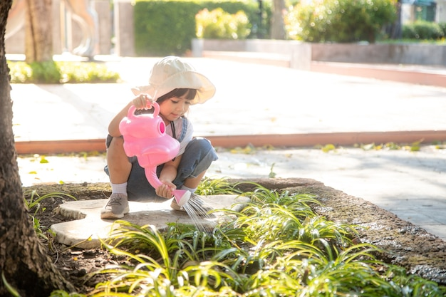 Petite fille asiatique versant de l'eau sur les arbres. kid aide à prendre soin des plantes avec un arrosoir dans le jardin.