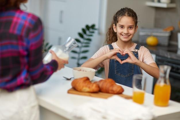 Petite fille assez frisée avec sa mère, regardant la caméra en souriant faisant la forme du symbole du coeur avec les mains.