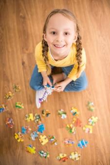 Petite fille assez souriante en pull assis sur le sol.