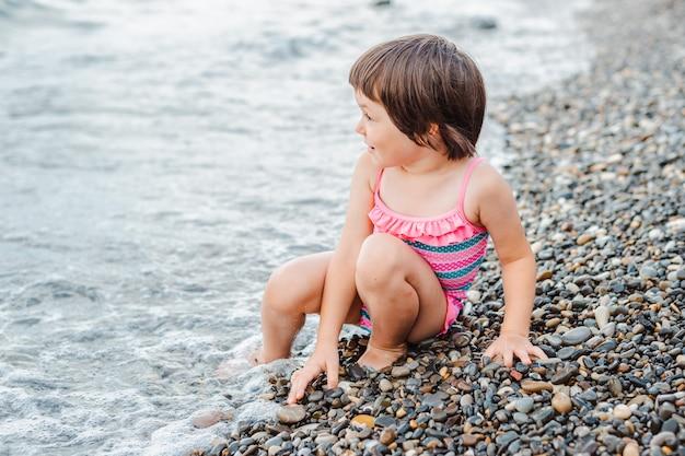Petite fille assise au bord de la mer