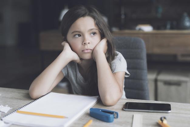 Petite fille assise au bureau montre une expression ennuyée