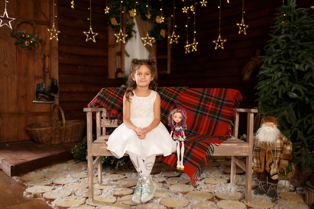 Petite fille assise sur un banc et tenir la poupée dans les mains