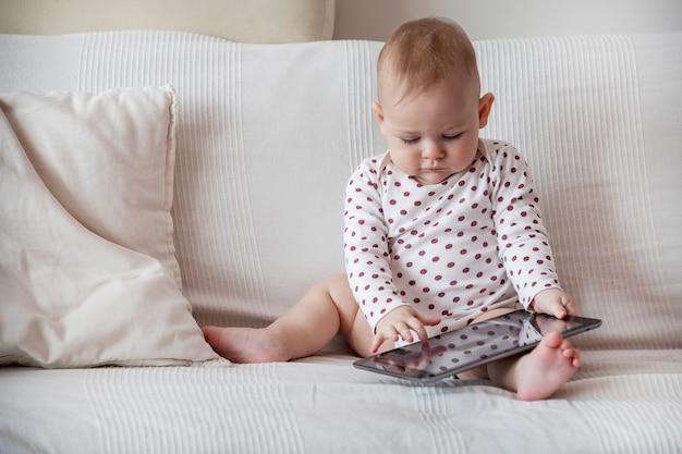 Petite fille assise sur un canapé blanc et tenant une tablette grise