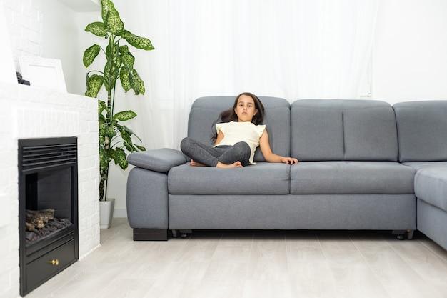 Petite fille assise sur un canapé et contrariée par quelque chose