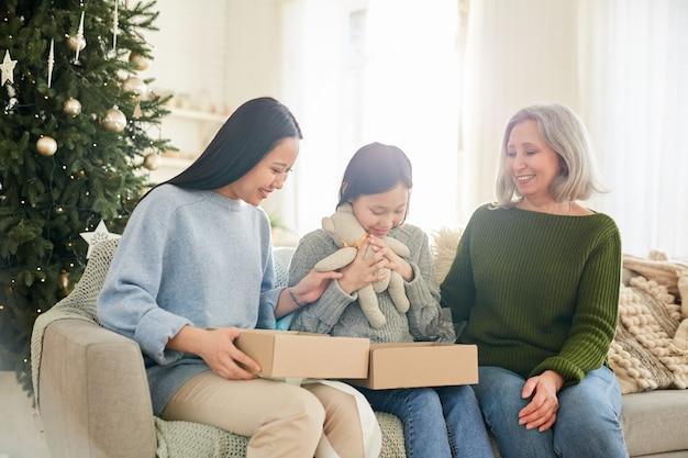Petite fille assise sur le canapé avec sa sœur aînée et sa mère, elle ouvre le cadeau de noël
