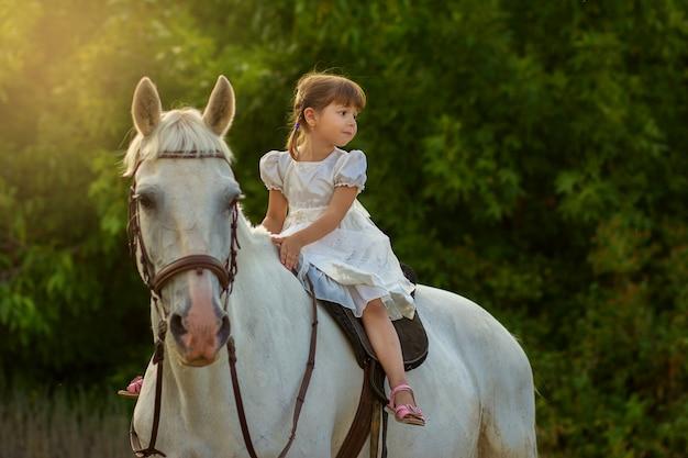 La petite fille assise sur un cheval à califourchon