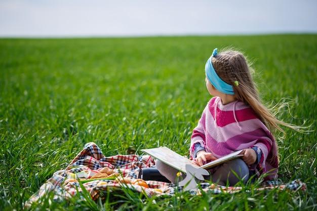 Petite fille assise sur un couvre-lit et lit un livre avec un conte de fées, herbe verte sur le terrain, temps de printemps ensoleillé, sourire et joie de l'enfant, ciel bleu avec nuages