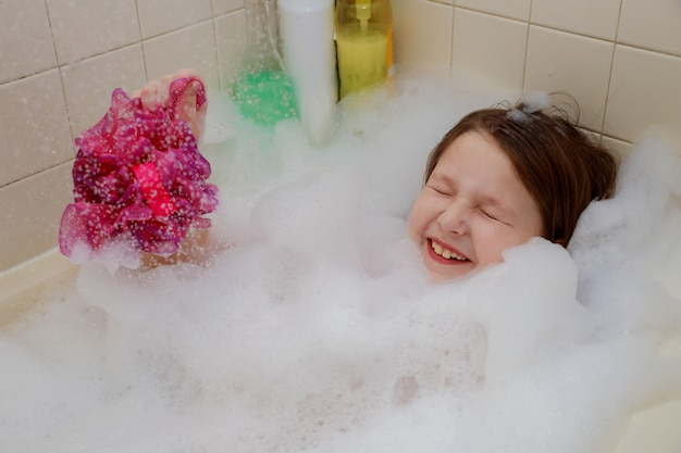 Une petite fille assise dans la baignoire jusqu'au cou, en s'amusant, souffle des bulles