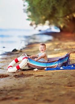 Petite fille assise dans un bateau, habillée en marin, sur une plage de sable avec des coquillages au bord de la mer