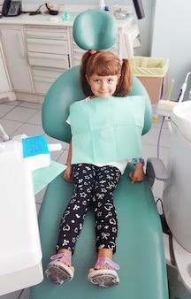 Petite fille assise dans le bureau des dentistes