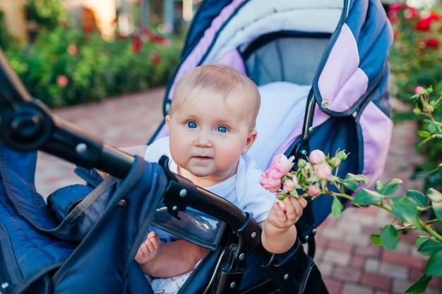 Petite fille assise dans une calèche et touchant des roses dans le jardin