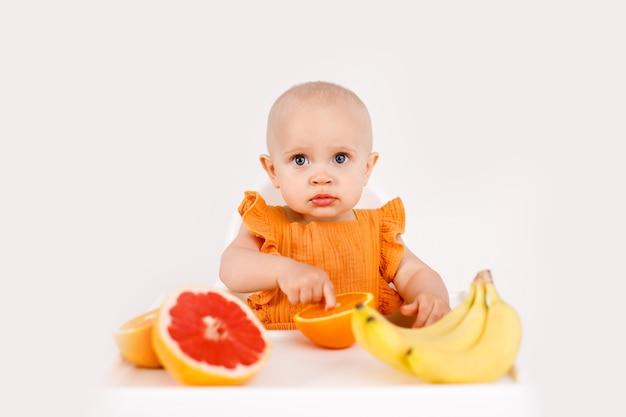 Petite fille assise dans une chaise haute pour enfant, manger des fruits sur blanc