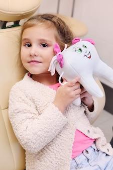 Petite fille assise dans un fauteuil dentaire tient une peluche sous la forme d'une dent.