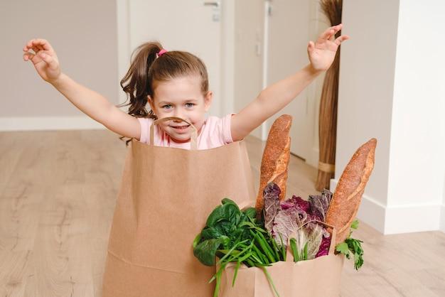 Petite fille assise dans un sac en papier se cachant avec des légumes et du pain, épicerie avec espace copie