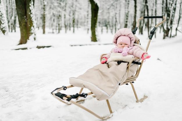 Une petite fille assise dans un traîneau pour enfants dans le parc.