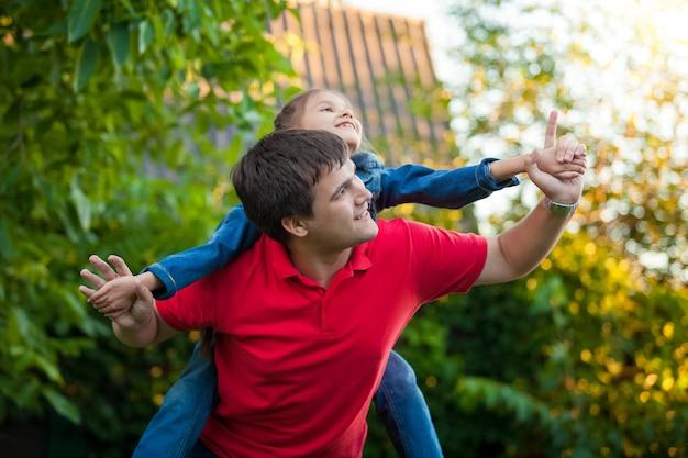 Petite fille assise sur les épaules du père et jouant avec lui