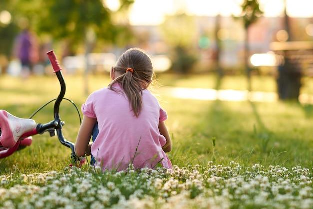 Petite fille assise sur l'herbe près de son vélo au coucher du soleil