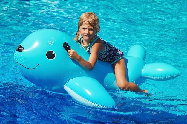 Petite fille assise sur le lion de mer gonflable dans la piscine